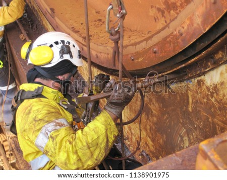 Closeup pictures of rope access miner abseiling working at height on rope using crow bar positioning himself, cleaning positioning  contaminated grease at construction mine site Perth, Australia