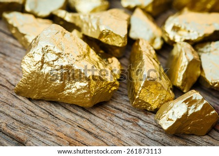 closeup pile of gold nugget on wooden table