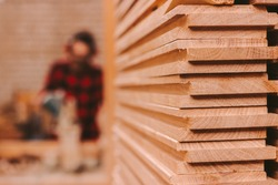 Closeup pile of wooden boards at lumber production factory. Stack of cut plywood at sawmill. Wooden material for furniture production at workshop. Carpenter using electrical circular saw on background