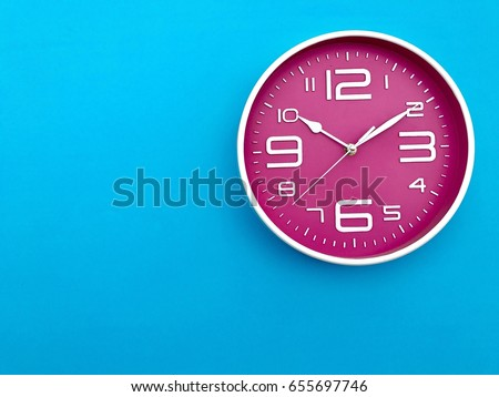 "Closeup pink wall clock  set on blue background. The concept of "" The time is going on."" Top view with Selective focus. Copy space."