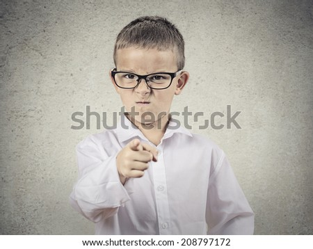Closeup portrait angry, mad child disguised as boss, executive businessman, pointing finger at someone, displeased, isolated grey background. Human face expressions, emotions, feelings, body language