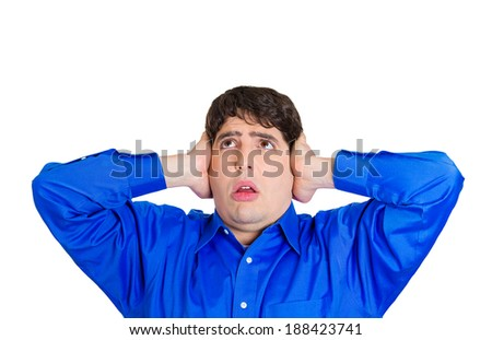 Closeup portrait, angry, unhappy, irritated young man covering ears, looking up, thinking stop making loud noise giving me headache, isolated white background. Negative emotion, face expression