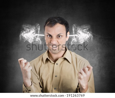 Closeup portrait angry young man, blowing steam coming out of ears, about to have nervous atomic breakdown, isolated black background. Negative human emotions, facial expressions, feelings, attitude