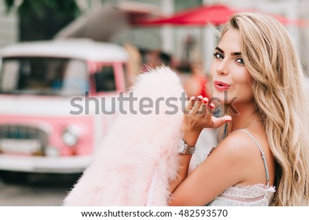 Closeup portrait attractive girl holding pink fur stole in hand on retro car background. She has long blonde hair, bare shoulder, sending a kiss to camera