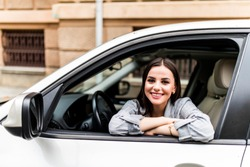 Closeup portrait attractive woman buyer sitting in her new car excited ready for trip isolated outside dealer dealership lot office. Personal transportation auto purchase concept