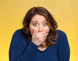 Closeup portrait beautiful, middle aged shocked young woman, covering her mouth, wide open eyes, isolated yellow background. Negative human emotion, facial expression, feeling, signs, symbol, reaction