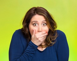 Closeup portrait beautiful, middle aged shocked young woman, covering her mouth, wide open eyes, isolated green background. Negative human emotion, facial expression, feeling, signs, symbol, reaction