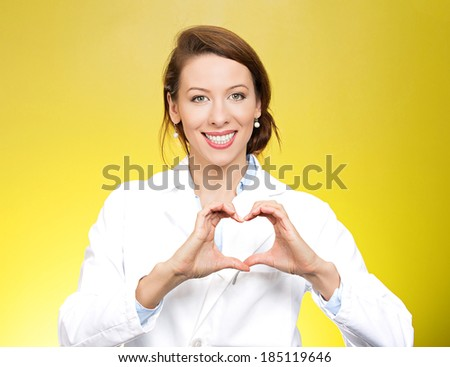 Closeup portrait, beautiful smiling cheerful health care professional, pharmacist, dentist, nurse making heart sign hands, isolated yellow background. Positive human emotion facial expression feeling