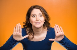Closeup portrait cautious, afraid, serious, annoyed displeased young woman raising hands up to say no, stop right there isolated orange background. Negative human emotion facial expression sign symbol