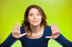 Closeup portrait cautious, afraid, serious, annoyed displeased young woman raising hands up to say no, stop right there isolated green background. Negative human emotion facial expression sign symbol