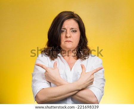 Closeup portrait confused middle aged woman pointing in two different directions, not sure which way to go in life isolated yellow background. Negative emotion facial expression feeling body language