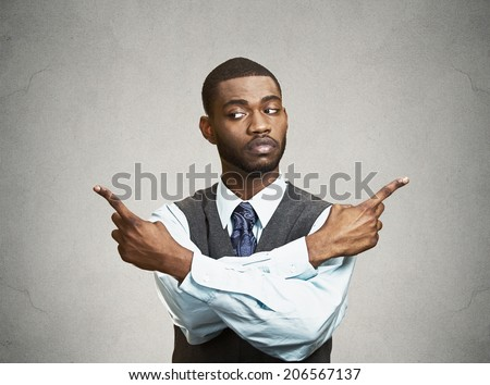 Closeup portrait confused young business man pointing in two different directions, not sure which way to go life, hesitant to make decision isolate black background. Emotion, facial expression feeling