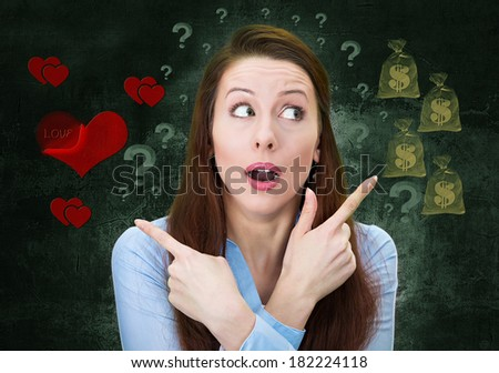 Closeup portrait confused young woman pointing in two different directions, not sure which way to go in life, isolated green background with dollar signs, red hearts. Emotion facial expression feeling