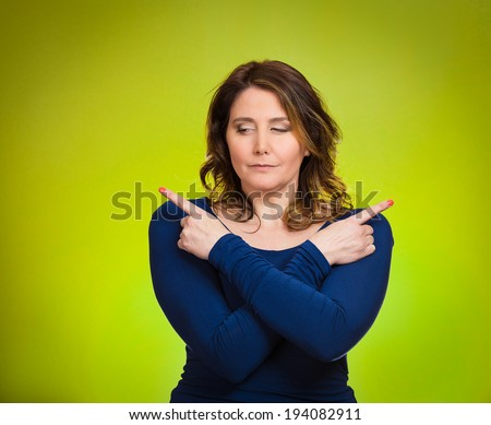 Closeup portrait confused young woman pointing in two different directions, not sure which way to go in life, isolated green background. Negative emotions, facial expressions, feeling body language