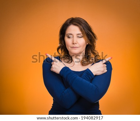 Closeup portrait confused young woman pointing in two different directions, not sure which way to go in life, isolated orange background. Negative emotions, facial expressions, feeling body language