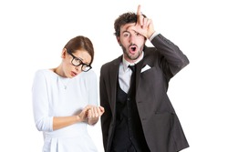 Closeup portrait couple, business people. Bully husband, man standing upfront, angry, giving bully sign with hand, shy, timid wife, nerdy woman with glasses, isolated white background. Human emotions