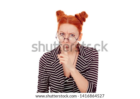 Closeup portrait cut out of a beautiful Secretive patronizing negative woman in her 30s with finger on lips asking shh, quiet wearing striped black white jacket with 2 buns up hairdo isolated on white