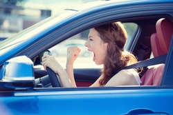 Closeup portrait displeased angry pissed off aggressive woman driving car shouting at someone hand fist up in air isolated traffic background. Emotional intelligence concept. Negative human expression