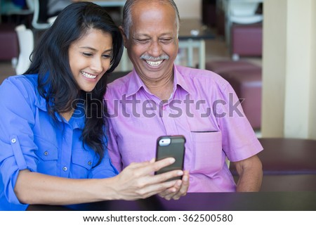 Closeup portrait elderly gentleman in pink shirt and lady in blue top family enjoying mobile phone fun, isolated indoors background