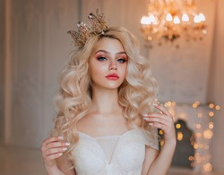 Closeup portrait elegant woman fantasy princess. Blonde girl long wavy hair. Beautiful face gentle makeup pink gloss lips shiny eyes. Evening festive look bride. Hairstyle gold crown holiday image