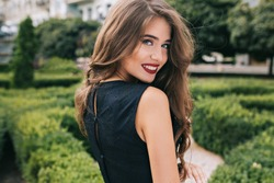Closeup portrait from back of pretty girl with attractive makeup and red lips on street on green yard background. She wears black dress, has long curly hair. She is smiling to camera.