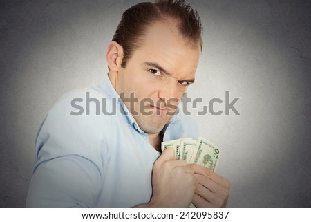 Closeup portrait greedy banker executive CEO boss, corporate employee funny looking man holding dollar banknotes scared to loose money, suspicious isolated grey background. Human face expression Stock photo ©