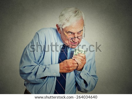 Closeup portrait greedy senior executive, CEO, boss, old corporate employee, mature man, holding dollar banknotes isolated on gray wall background. Negative human emotion facial expression  Foto stock ©