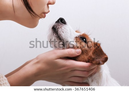 Closeup portrait handsome young hipster woman, kissing her good friend dog on grey background. Positive human emotions, facial expression, feelings