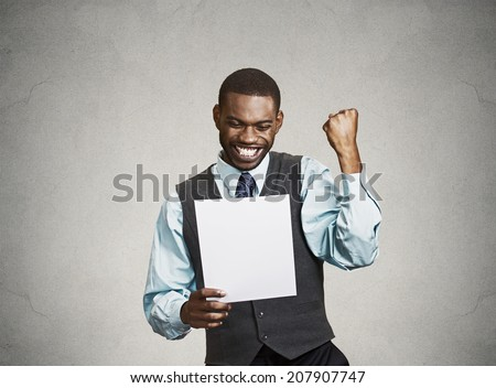 Closeup portrait happy excited young business man executive looking monthly statement glad to pay off bills isolated grey background. Positive emotion facial expression. Financial success good news