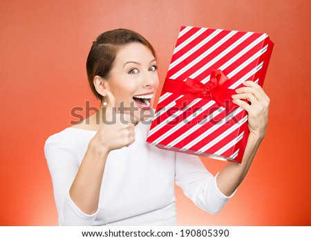 Closeup portrait happy, excited young woman about to open, unwrap red birthday gift box, giving thumbs up isolated red background. Positive emotions, facial expressions, feelings, attitude, reaction