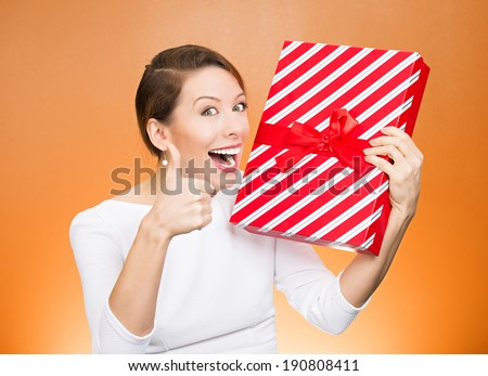 Closeup portrait happy, excited young woman about to open, unwrap red birthday gift box, giving thumbs up isolated orange background. Positive emotions, facial expression, feelings, attitude, reaction
