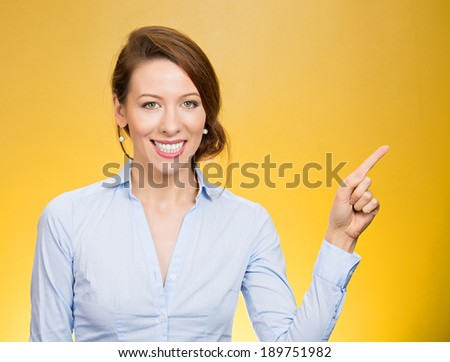 Closeup portrait, happy, pretty, confident, young smiling woman gesturing pointing to space at left, isolated yellow background. Positive human emotion signs symbol, facial expression feelings