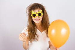 Closeup portrait happy, smiling, funny looking little girl with sunglasses, holding orange balloon and needle about to burst bubble, isolated background. Human face expressions, emotions, feelings