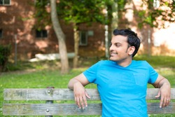 Closeup portrait, happy smiling, regular young man in blue shirt sitting on wooden bench, relaxed looking to side, isolate background trees, woods