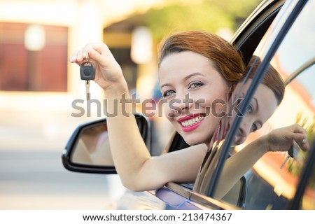 Closeup portrait happy, smiling, young attractive woman, buyer sitting in her new blue car showing keys isolated outside dealer, dealership lot, office. Personal transportation, auto purchase concept