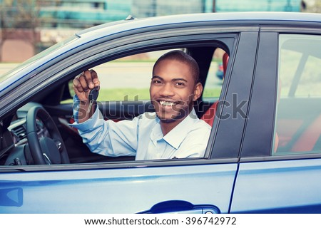 Closeup portrait happy, smiling, young man, buyer sitting in his new blue car showing keys isolated outside dealer, dealership lot. Personal transportation, auto purchase concept