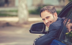 Closeup portrait happy smiling young man buyer sitting in his new car excited ready for trip. isolated outside dealer dealership lot office. Personal transportation auto purchase concept