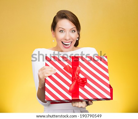 Closeup portrait happy, super excited young woman about to open, unwrap red birthday gift box, isolated yellow background. Positive human emotions, facial expressions, feelings, attitude, reaction