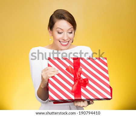 Closeup portrait happy, super excited young woman, lady about to open, unwrap birthday gift box, isolated yellow background. Positive human emotions, facial expressions, feelings, attitude, reaction