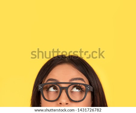 closeup portrait headshot cropped face above lips of cute happy woman in glasses looking up isolated on yellow studio wall background with copy space above head. Human face expressions, emotions #1431726782