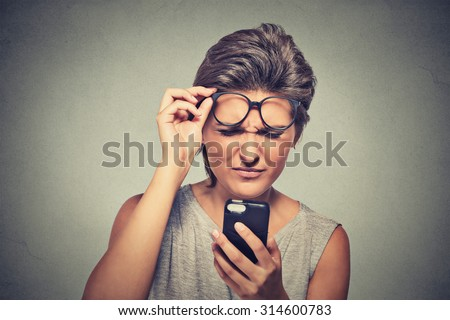 Closeup portrait headshot young woman with glasses having trouble seeing cell phone has vision problems. Bad text message. Negative human emotion facial expression perception. Confusing technology