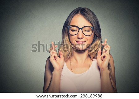 Shutterstock Closeup portrait hopeful beautiful woman crossing her fingers, eyes closed, hoping, asking best isolated on gray wall background. Human face expression, emotions, feeling attitude reaction