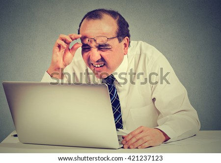 Closeup portrait middle aged business man with glasses having eyesight problems confused with laptop software isolated on gray background. Age related changes. Human face expression