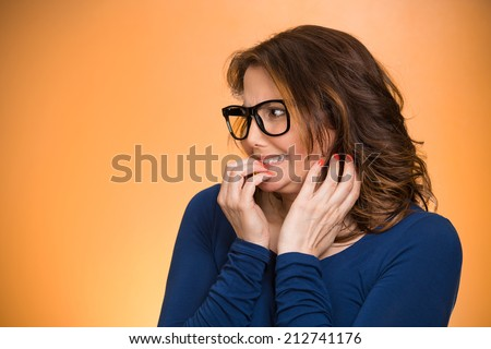 Closeup portrait nervous woman with glasses biting her fingernails craving something, anxious isolated orange background copy space. Negative human emotion facial expression body language perception