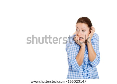 Closeup portrait of a anxious young beautiful woman biting her finger nails looking sideways secretly craving for something, isolated on white background, copy space to left. Human emotion, expression