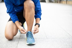Closeup portrait of a Athlete wearing a blue Windbreaker jacket.,during training tying shoelaces on sporty sneaker . Sport and running idea concept.
