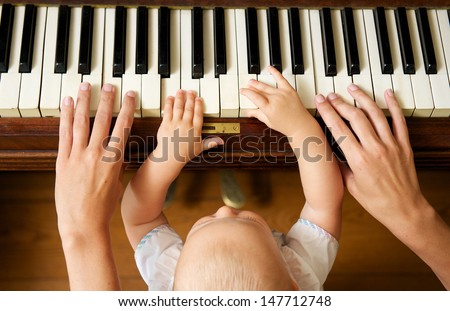 Closeup portrait of a baby learning to play piano with mother from above