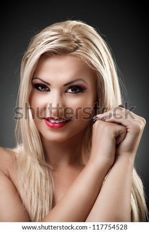 Closeup portrait of a beautiful blond woman holding hands near her face