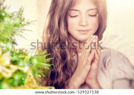 Shutterstock Closeup portrait of a beautiful calm girl with closed eyes praying near Christmas tree, gentle young angel wishing peace and harmony for everyone, happy religious holiday