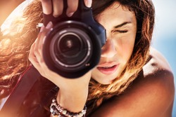 Closeup portrait of a beautiful girl with camera on the beach, cute young photographer taking picture, creative hobby, happy active summer vacation